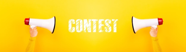 Megaphones and inscription contest on yellow background, panoramic image