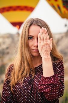 Mehendi手で目を覆っている若い魅力的な女性