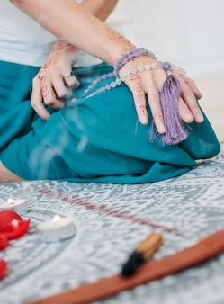彼女の手にライラックのマラビーズを持つ女性ヘナmehendi