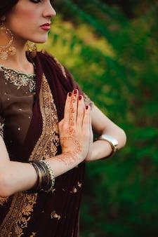 멘디는 아름다운 인도 여자의 손을 커버