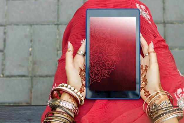 Красивая женщина носить традиционные мусульманские арабские индийские свадьбы красное розовое платье руки сари с ювелирными изделиями и браслетами картины mehndi татуировки хны держит таблетку. концепция праздника фестиваля культуры лета.