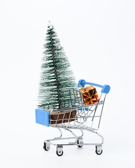 Meiallic shopping cart with gift and miniature christmas tree isolated on white surface, christmas and new year