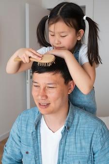 Meidum shot ragazza che spazzola i capelli del padre