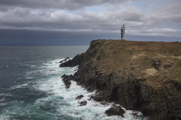 Маяк мейрас на скалах валдовино в окружении моря под пасмурным небом в галисии, испания