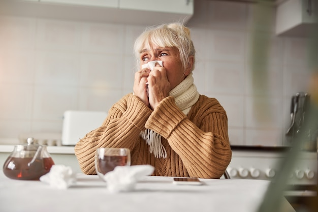 Melancholic aged lady having a seasonal cold and staying home