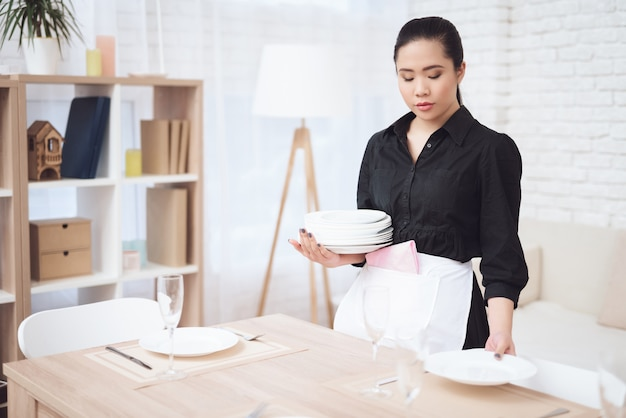 Melancholic housekeeper sets table in hotel room