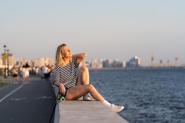Меланхоличная женщина наслаждается летним закатом, сидя на берегу реки с лонгбордом в одиночестве, чувствуя свободу
