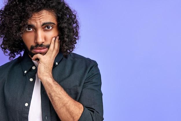 우울한 아랍 남자는 슬픔으로 보이며 캐주얼 셔츠를 입은 젊은 남성은 뉴스에 화를 냈습니다. 보라색 벽에 절연