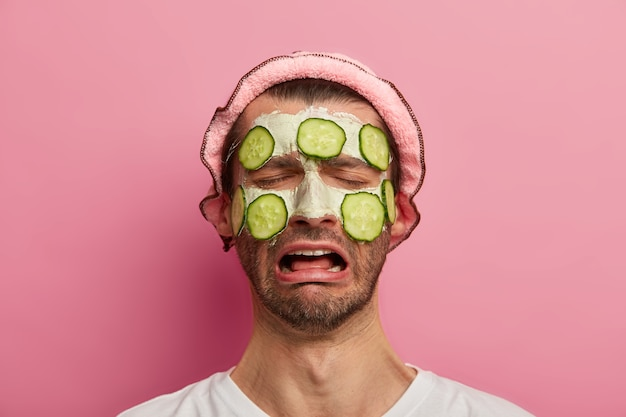 Melancholy male model has homemade mask with cucumbers on face, tired of visiting spa salon, wears white t shirt and bath hat, cannot feel relaxed