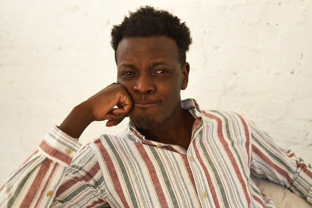Melancholy, sadness and depression concept. close up shot of sad upset young dark skinned guy looking at camera with thinned lips having sorrowful facial expression