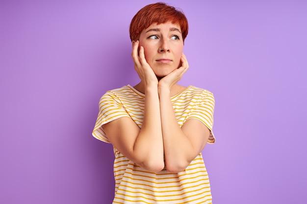 우울한 여자는 슬픈 감정을 느끼고 얼굴을 만지고 측면을 바라보고 서 있습니다.