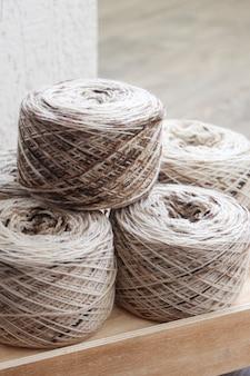 Melange yarn skeins on a wooden box in a light room