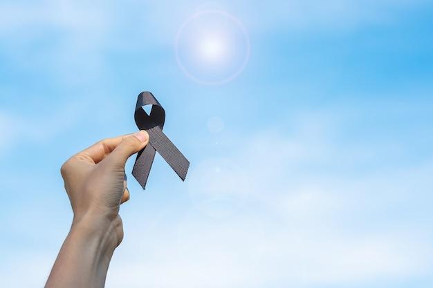 黒色腫と皮膚がん、ワクチン傷害の認識月間、そして平和の概念で休む。空の背景に黒いリボンを保持している男