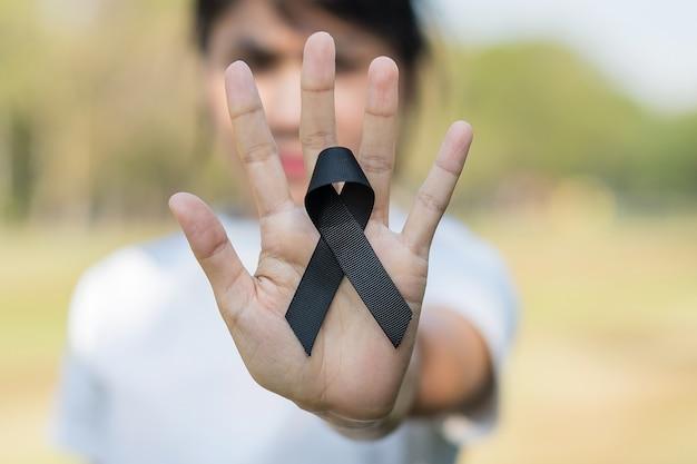 黒色腫と皮膚がん、ワクチン傷害の認識月間、そして平和の概念で休む。黒のリボンを持っている女性