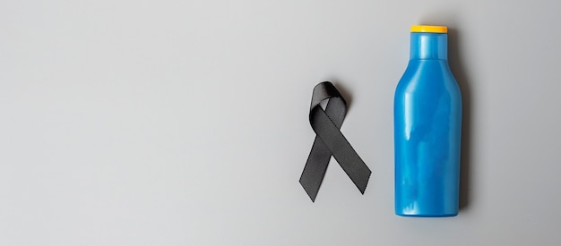 Melanoma and skin cancer awareness month. black ribbon and body sunscreen bottle on grey background. world cancer day concept