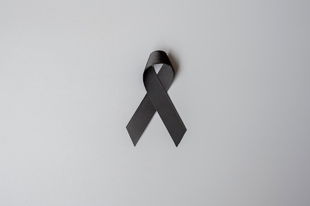 Melanoma and skin cancer, vaccine injury awareness month and rest in peace concepts. black ribbon on grey background