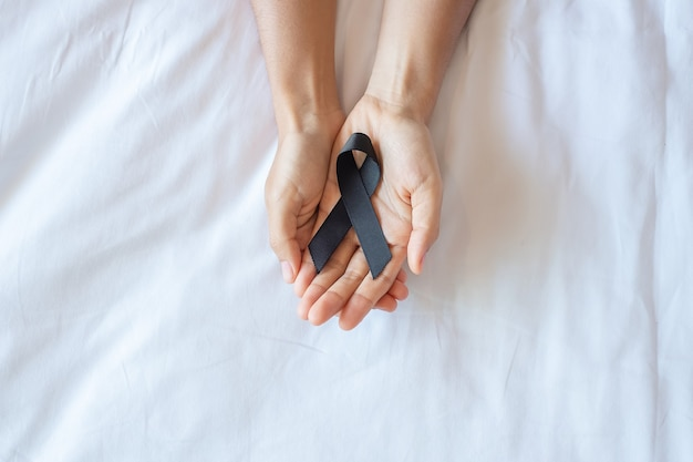 Melanoma and skin cancer, vaccine injury awareness month and rest in peace concepts. man holding black ribbon on white bed background