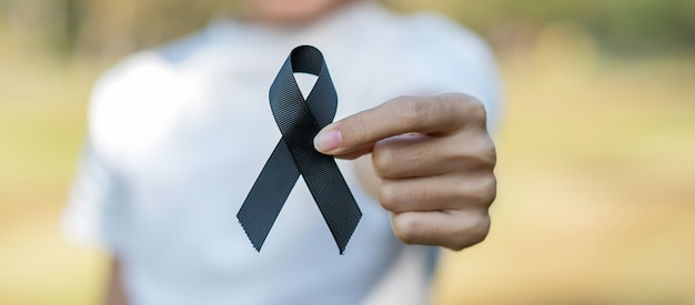 Melanoma and skin cancer, vaccine injury awareness month and rest in peace concepts. woman holding black ribbon