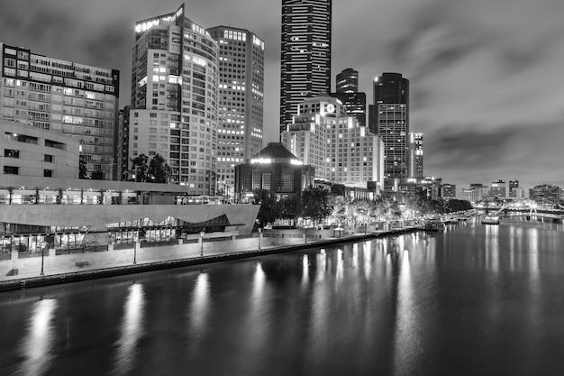 メルボルン、オーストラリア-2014年12月11日:夕暮れ時のヤラ川沿いのメルボルンのスカイラインの白黒画像。メルボルンはビクトリア州の州都で最も人口の多い都市です