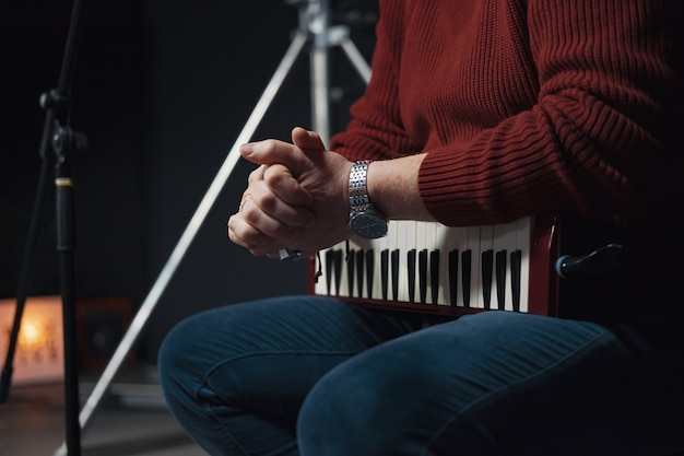 人間の手にある鍵盤ハーモニカ、管楽器、スタジオでの音楽の録音