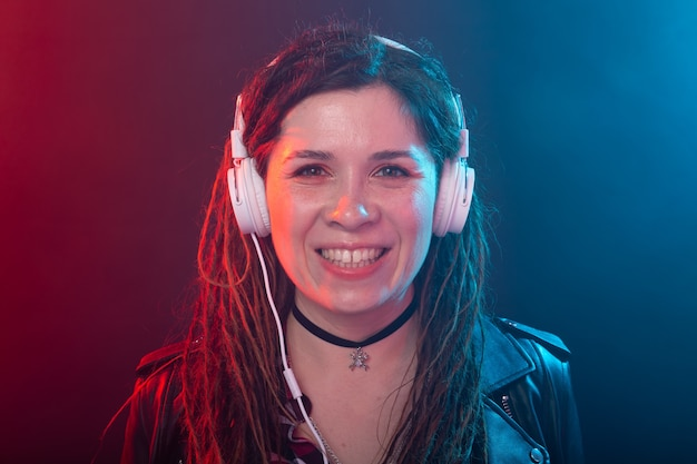 Концепция меломана, музыки и людей - молодая женщина с дредами слушает музыку и наслаждается ею