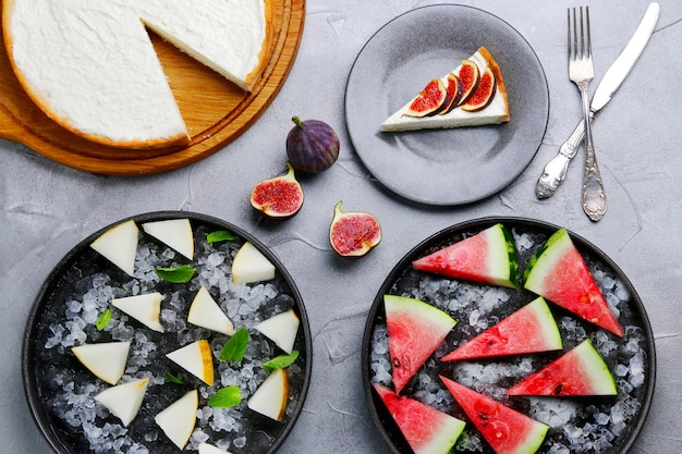 メロンとスイカのプレートとチーズケーキの上面図。軽いコンクリートのテーブルの上の秋または夏のデザート。