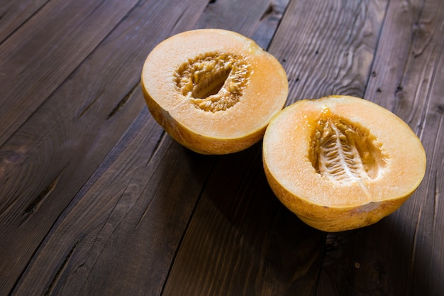 Melon cut in half on a wooden surface