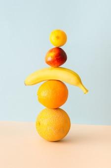 Дыня, апельсин, банан, нектарин и лимон стоят друг на друге на синем и кремовом фоне. творчески организованная концепция летнего фруктового смузи.