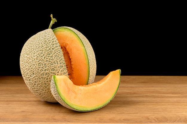 Melon fruit sliced on wooden table with black background