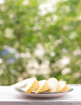 Melon slices on a white wooden table, green trees on the background. healthy food.