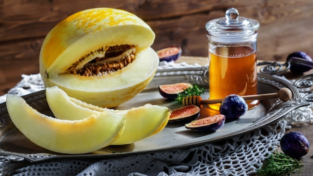 Melon with honey,  figs, on a rustic wooden table