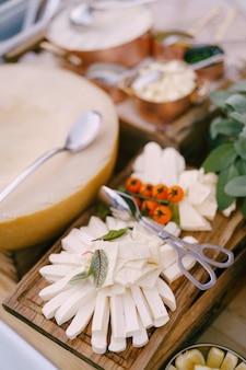 Плавленый сыр и веточка помидоров черри на деревянной доске с дыней на размытом фоне