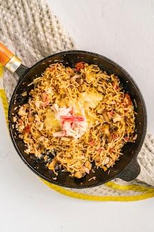 Плавленый сыр на сковороде с макаронами впагетти и морепродуктами, вид сверху