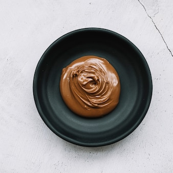 흰색 배경 위에 검은 그릇에 녹은 초콜릿