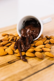 Melted chocolate pouring from cup on almonds