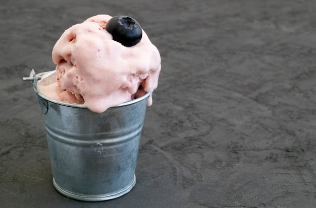 Melted ice cream in a bucket of blueberry.