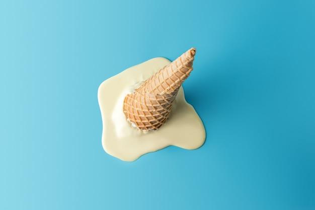 パステルブルーのアイスクリームコーンと溶けたアイスクリーム