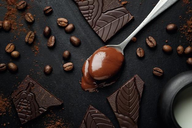 暗い表面に壊れたチョコレートとコーヒー豆をスプーンで溶かします