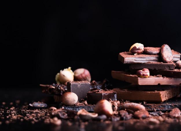Тающий шоколад или растопленный шоколад с шоколадным вихрем и стопкой, чипсами и порошком на темном столе