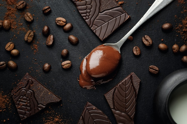 Melting chocolate in spoon with broken chocolate and coffee beans around on dark surface