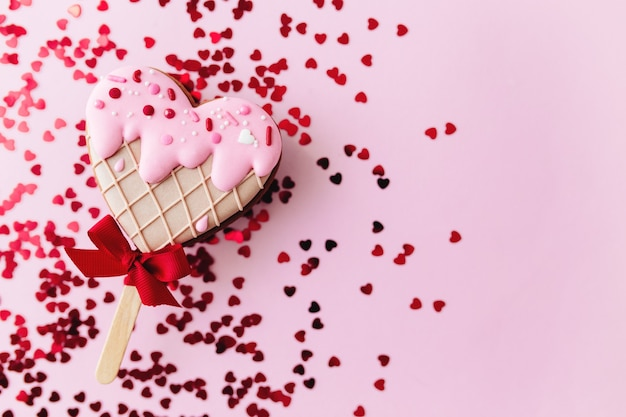 Melting ice cream heart gingerbread cookie. valentine. pink background, glitter. high quality photo