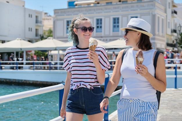 歩く母と娘の笑顔の手でアイスクリームを溶かす