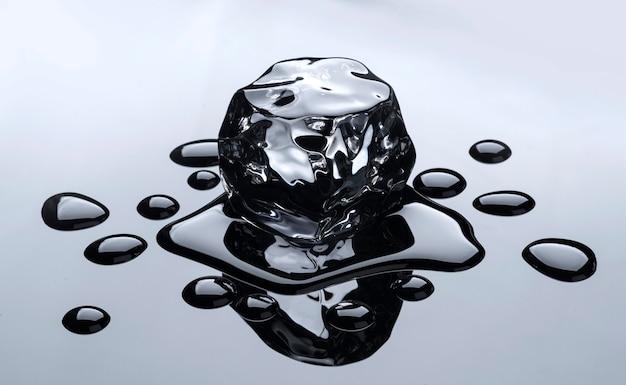 검은 거울 배경에 물 방울과 녹는 아이스 큐브
