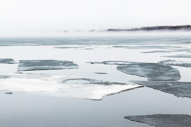 Тающий лед на берегу озера туманным утром. красивый весенний пейзаж.