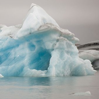 Melting iceberg in glacial lake, with an ice cave