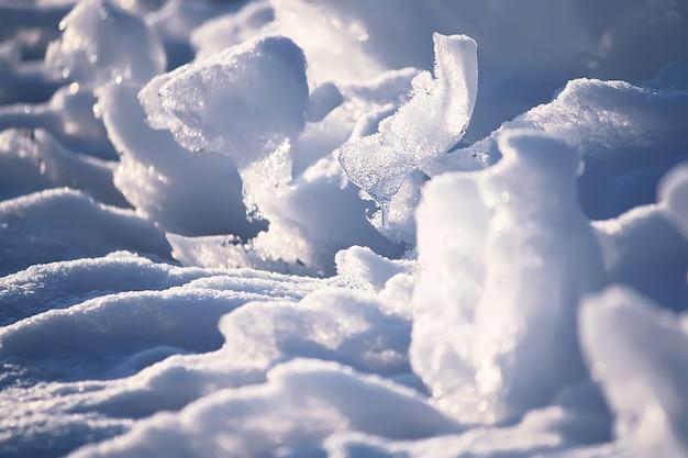 冬の夕方の日差しに溶ける雪と氷の表面がクローズアップ
