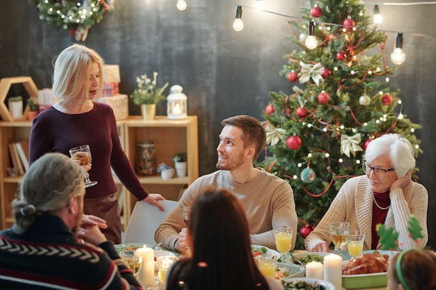 Members of big family looking at mature blonde woman with glass of wine making christmas toast by festive dinner