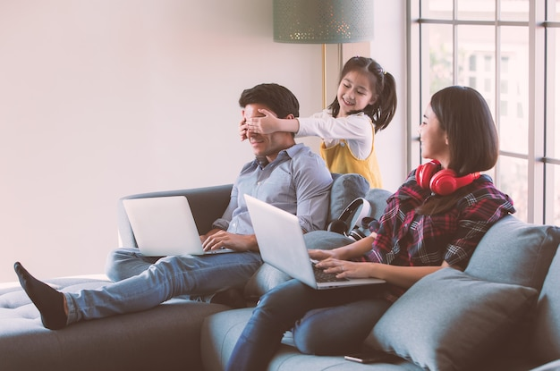 Members of diverse family, caucasian father and asian mother using laptop computer notebook to work from home, young cute little girl daughter come to kidding her dad by closing his eyes with hands.