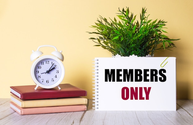 Members only is written in a notebook next to a green plant and a white alarm clock, which stands on colorful diaries.