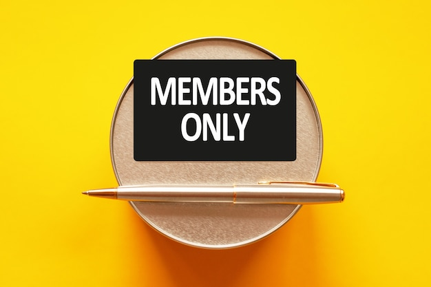 Members only- words writing a white letters on a sheet paper. black card with text on a yellow wall with round metal stand and metal writing pen. business, finance and education concept